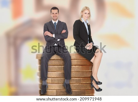 Full length of confident young business people sitting on stacked coins - stock photo