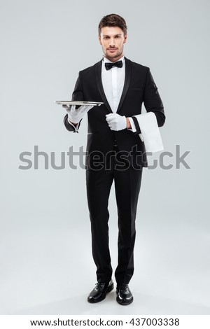 Full length of confident young waiter in tuxedo standing and holding tray over white background - stock photo