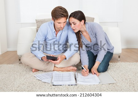 Full length of couple calculating budget in living room at home - stock photo