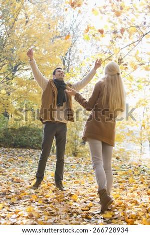 Full length of couple enjoying in autumn - stock photo