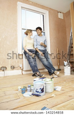 Full length of couple holding coffee mugs while looking at each other with paint cans in foreground - stock photo
