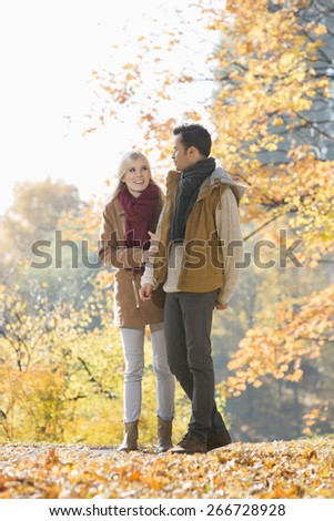 Full length of couple walking in park during autumn - stock photo