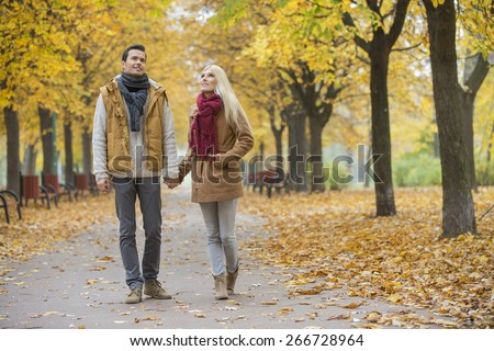 Full length of couple walking while looking up in park during autumn - stock photo
