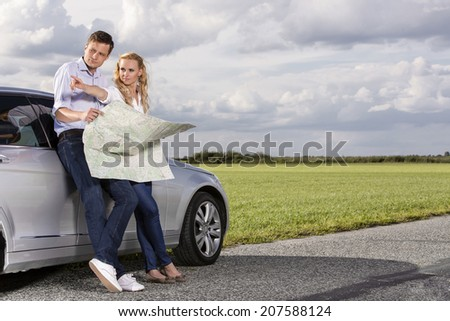 Full length of couple with map discussing direction while leaning on car at countryside - stock photo