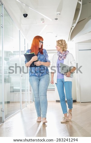 Full-length of creative businesswomen conversing while walking at office hallway