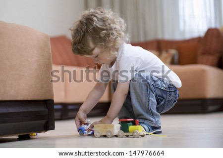 Full length of cute boy playing with toy train in living room - stock photo