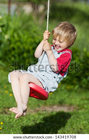 Full length of cute boy swinging in playground - stock photo