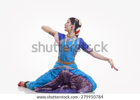 Full length of dancer in traditional wear performing Bharatanatyam against white background - stock photo