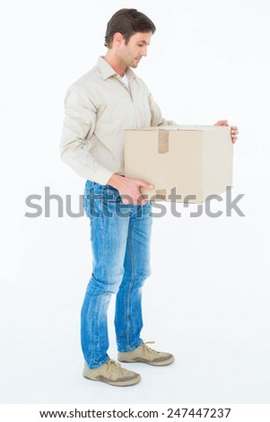 Full length of delivery man carrying cardboard box against white background
