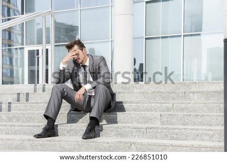 Full length of depressed businessman sitting on steps outside office - stock photo