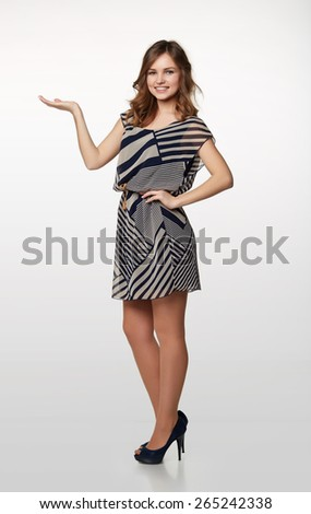 Full length of elegant business woman showing holding on the palm blank copy space over gray background - stock photo