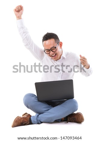 Full length of excited Asian businessman hand raise looking at laptop sitting over  white background - stock photo