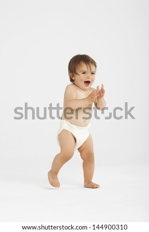 Full length of excited baby girl taking first step on white background - stock photo