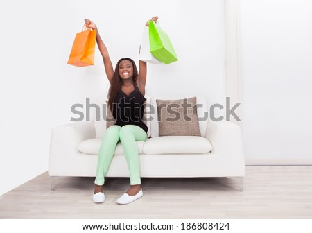 Full length of excited woman carrying shopping bags while sitting on sofa in living room - stock photo