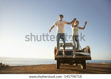 Full length of excited young couple jumping from back of van parked by ocean - stock photo