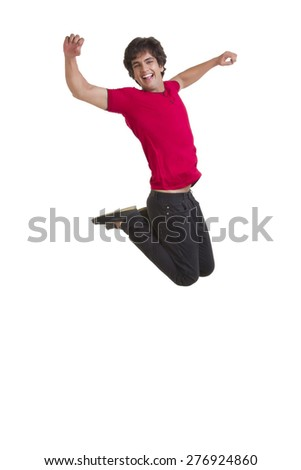 Full length of excited young man jumping with arms raised over white background - stock photo