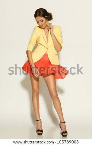 Full length of fashion model posing in mini skirt fluttering on the wind - stock photo