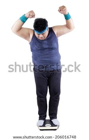 Full length of fat man measure his body - stock photo