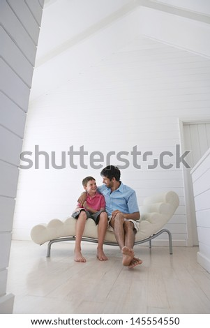 Full length of father and son sitting on lounge chair looking at each other - stock photo