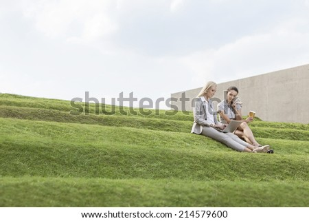 Full length of female business executives with disposable coffee cup and laptop sitting on grass steps against sky - stock photo