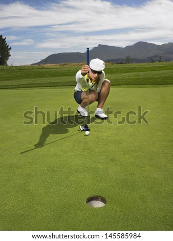 Full length of female golfer lining up a putt in golf course - stock photo