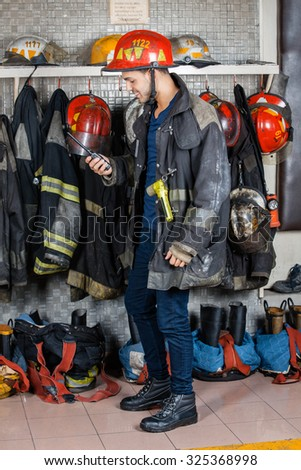 Full length of firefighter looking at walkie talkie against uniforms hanging in fire station - stock photo