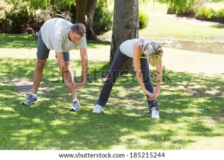 Full length of fit couple exercising in the park - stock photo