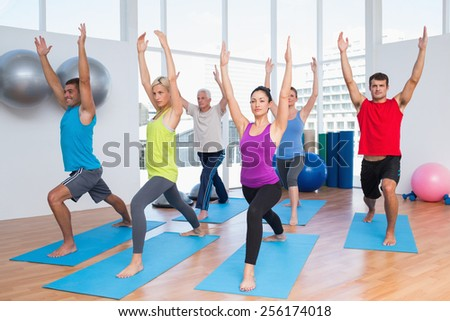 Full length of fit men and women exercising with hands raised at fitness club