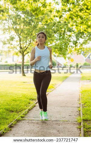 Full length of fit young woman jogging through the park