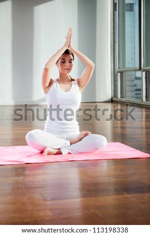 Full length of fit young woman practicing yoga on mat at gym