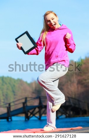 Full length of fitness woman sport teenage girl in pink tracksuit showing blank copy space screen of tablet touchpad computer outdoor. Electronic technology. - stock photo