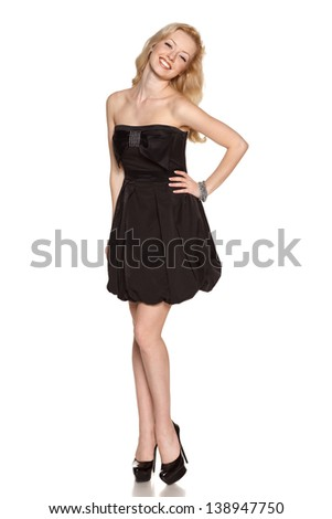 Full length of flirtatious woman with radiant smile wearing black cocktail dress with hand on hip looking at camera, isolated on white background - stock photo