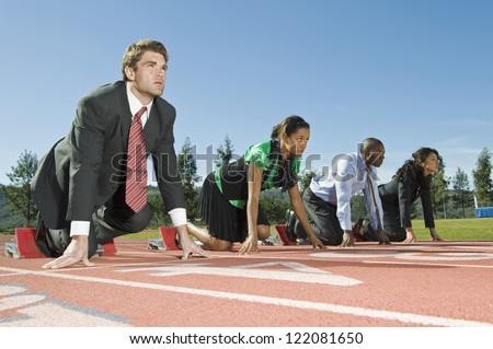 Full length of four multi ethnic businesspeople at starting position on race track - stock photo