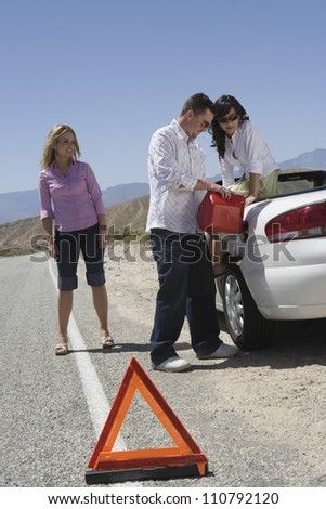 Full length of friends refueling car with warning triangle in the foreground - stock photo