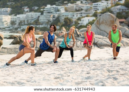 Full length of friends stretching at beach