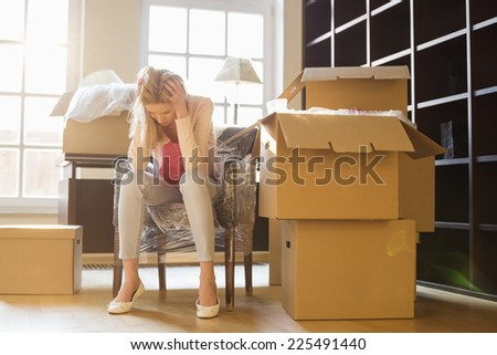 Full-length of frustrated woman sitting by cardboard boxes in new house - stock photo