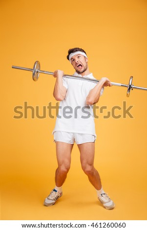 Full length of funny young fitness man holding heavy barbell over yellow background
