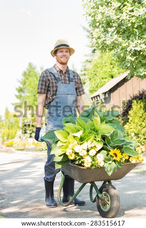 Full-length of gardener pushing wheelbarrow with plants at garden