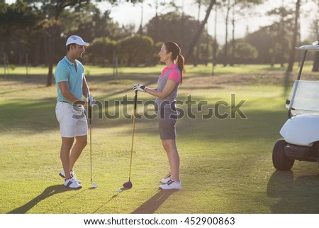 Full length of golf player couple standing on field