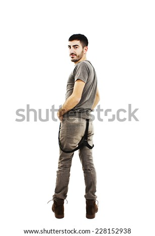 Full length of handsome young man smiling, looking over a shoulder. Isolated on a white background  - stock photo