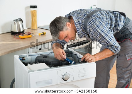 Full length of handyman checking washing machine with flashlight in kitchen