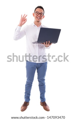 Full length of happy Asian businessman using laptop showing okay hand sign standing isolated over  white background - stock photo