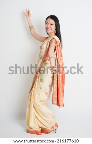 Full length of happy Asian Indian girl dancing on plain background. - stock photo