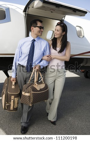 Full length of happy business couple walking together with airplane in the background at airfield - stock photo