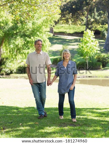 Full length of happy couple walking while holding hands in park - stock photo