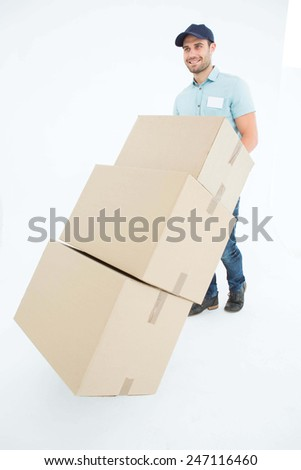 Full length of happy delivery man pushing trolley of boxes on white background - stock photo