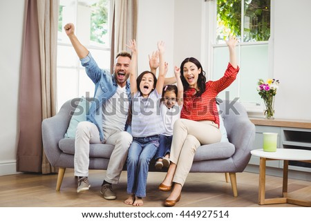 Full length of happy family cheering while siting on sofa at home - stock photo