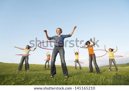 Full length of happy female friends playing with hula hoop against sky in park - stock photo