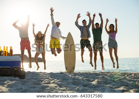 Full length of happy friends jumping on shore at beach