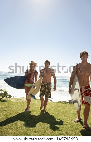 Full length of happy friends with surfboards walking away from ocean - stock photo